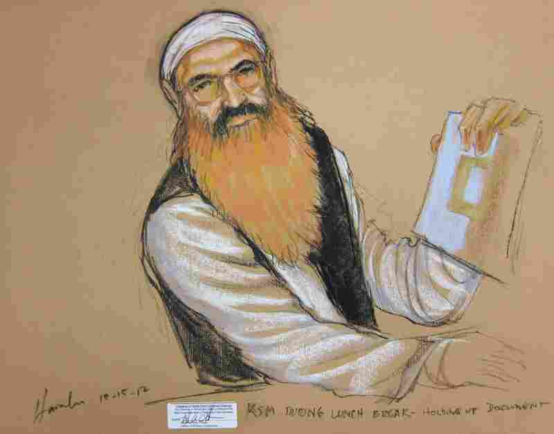 Khalid Sheikh Mohammed — accused of being the mastermind of the Sept. 11 attacks — holds up a piece of paper in this artist's sketch during a court recess at a pretrial hearing at Guantanamo Bay in October 2012.