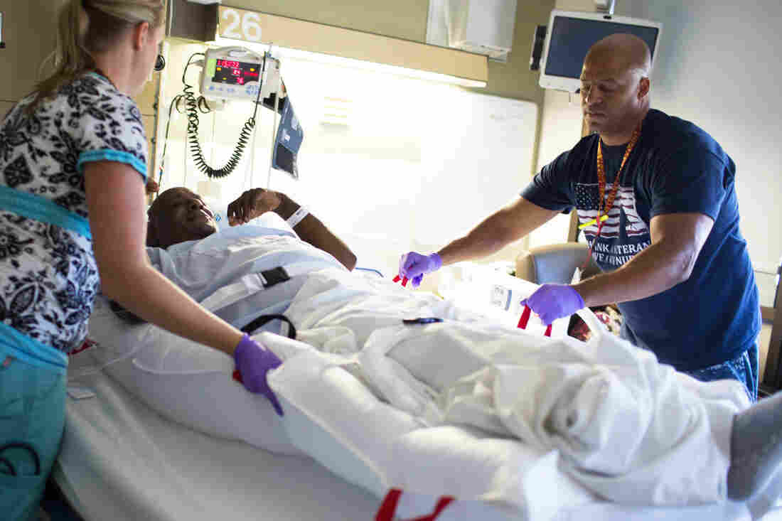 Joleen Beiley and Stephen Gafford lift patient David Eurey using a floating mattress called a HoverMatt, which uses air streams that lift the mattress, making it easy for nursing employees to move a patient from a bed to a gurney.
