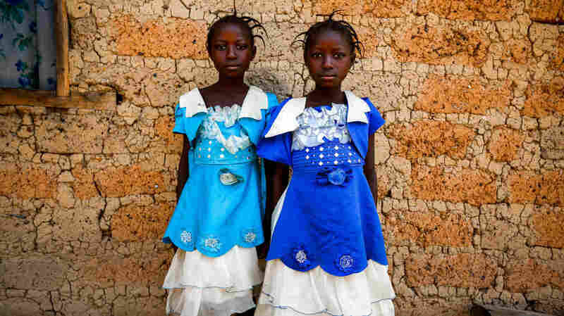 Twins Watta and Fatta Balyon pose for a picture outside their guardian Mamuedeh Kanneh's house.