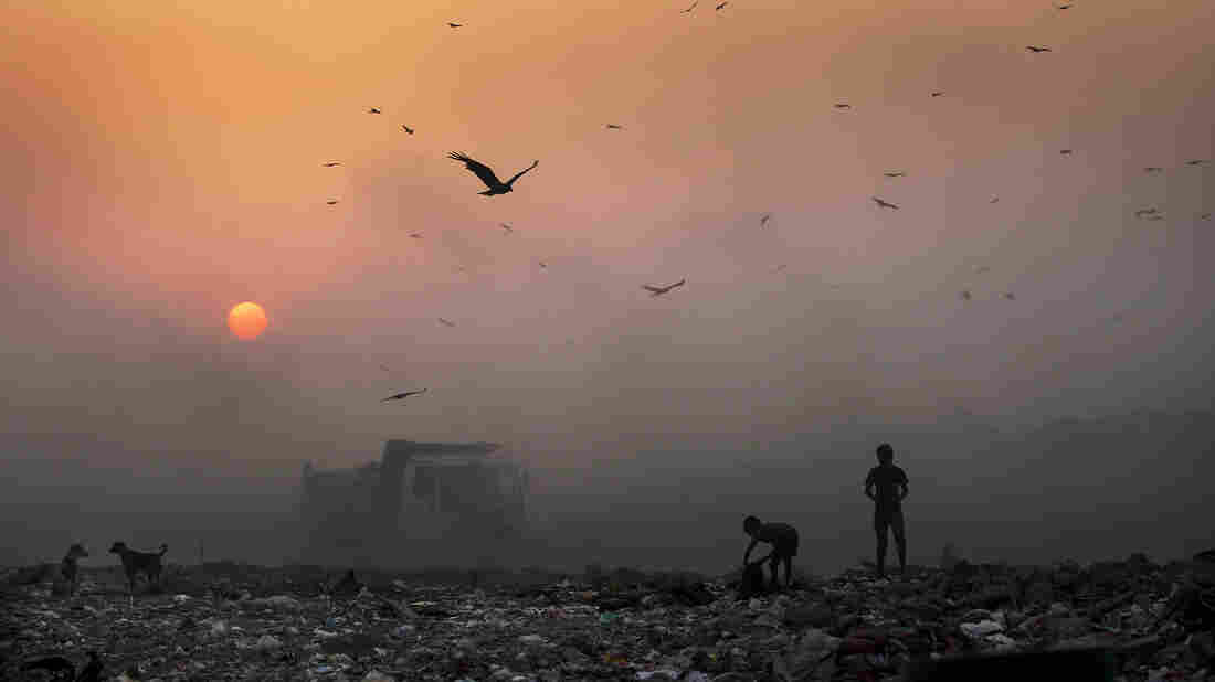 Smoke blankets the setting sun as young ragpickers search for reusable material at a garbage dump in New Delhi, India.