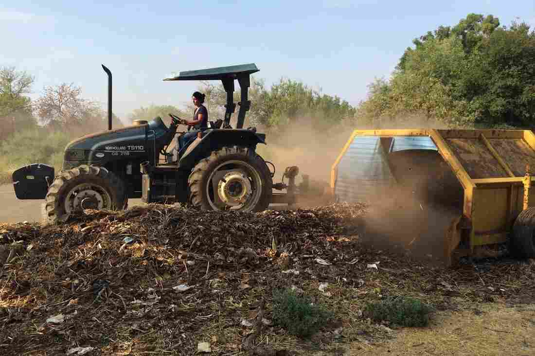 Former Director Nidhi Solanki of Project Compost uses a tractor and compost turner to turn food waste into compost.
