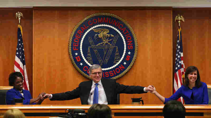At the start of a meeting to decide the issue of net neutrality, Federal Communications Commission Chairman Tom Wheeler (center) holds hands with FCC Commissioners Mignon Clyburn (left) and Jessica Rosenworcel at the FCC headquarters Thursday.