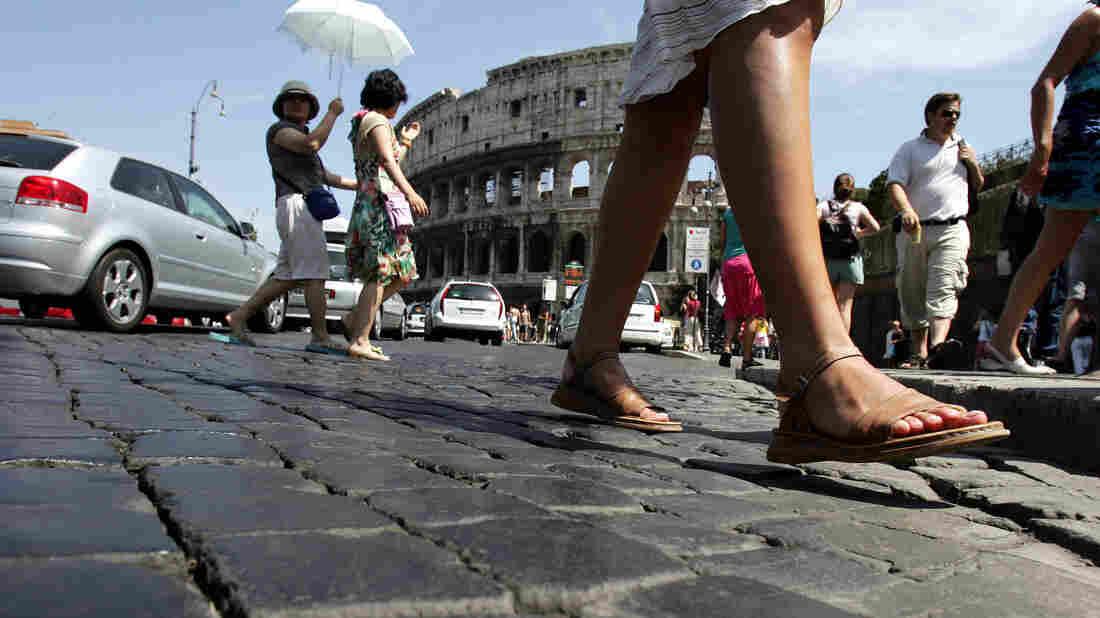 Pedestrians cross the cobblestone Via dei Fori Imperiali in front of Rome's Colosseum.