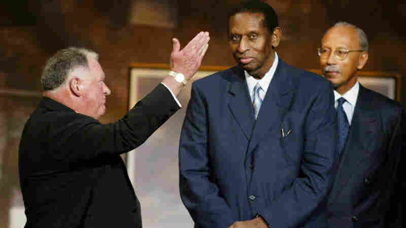 Earl Lloyd, who became the first black player to play in the NBA in 1950, died Thursday at 86. He's seen here, center, being inducted into the Basketball Hall of Fame's Honors Ring in 2003.