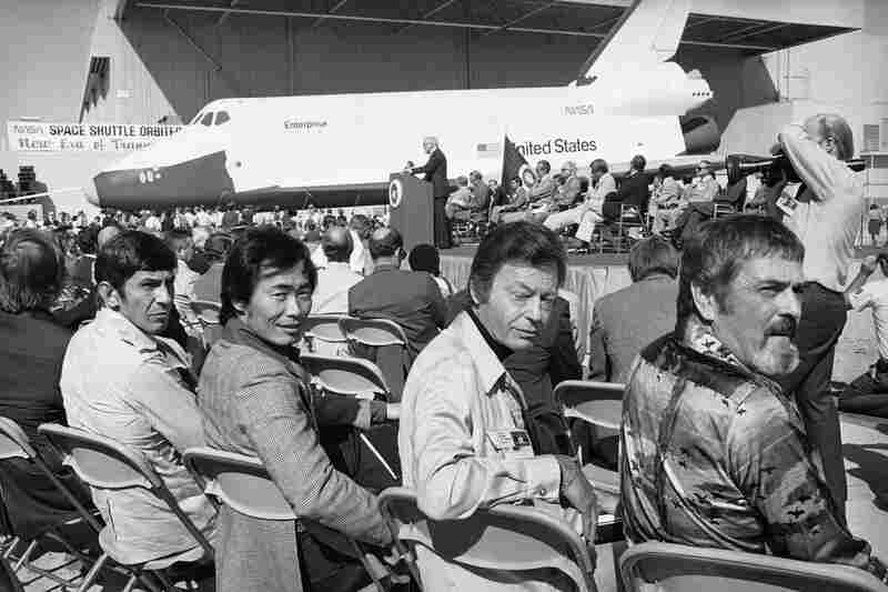 The space shuttle is shown in the background after its unveiling in Palmdale, Calif., in September 1976. In the foreground is the crew of the television series Star Trek, whose ship was also named Enterprise. They are Leonard Nimoy (from left), who portrayed Mr. Spock; George Takei, who played Mr. Sulu; DeForest Kelley, who played Dr. McCoy; and James Doohan, who played Scotty.