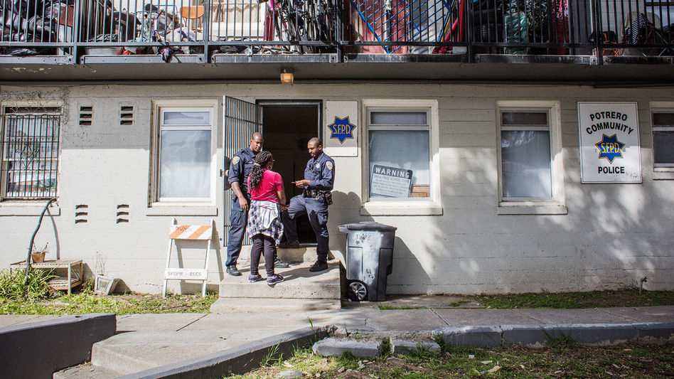 Uzuri Pease-Greene talks with two police officers in the public housing complex in San Francisco where she lives. (Talia Herman for NPR)