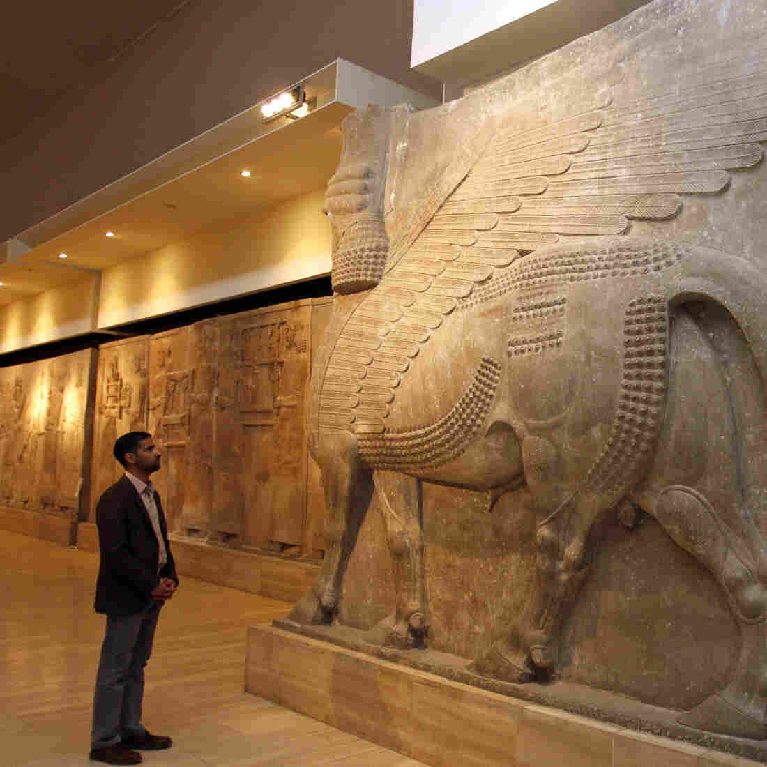 A man looks at ancient Assyrian human-headed winged bull statues at the Iraqi National Museum in Baghdad on Saturday.