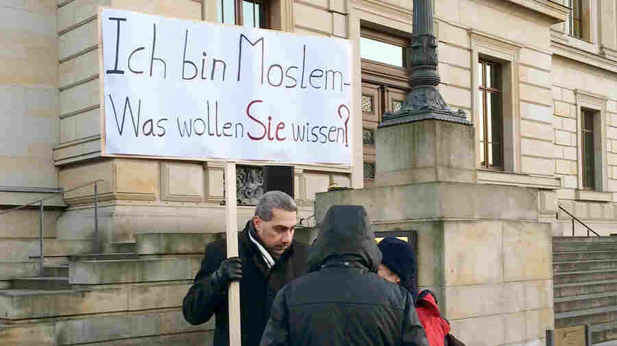 """Earlier this month, Dr. Sadiqu al-Mousllie, accompanied by his family and a few members of their mosque, stood in downtown Braunschweig, Germany, and held up signs that read: """"I am a Moslem. What would you like to know?"""" in an effort to promote dialogue between Muslims and non-Muslims."""