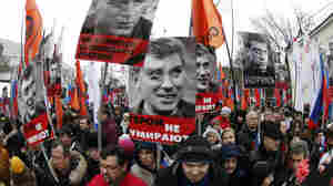 People hold flags and posters during a march to commemorate Kremlin critic Boris Nemtsov, who was shot dead on Friday night.