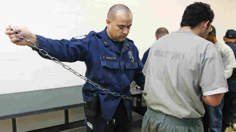 Corrections officer Sgt. Charles Galaviz secures an inmate for transfer with handcuffs and shackles Jan. 24 at the Lexington Assessment and Reception Center, in Lexington, Okla. Overtime is mandatory for correctional officers in the state's prisons, which have a manpower shortage of about 33 percent and the highest inmate homicide rate in the country.