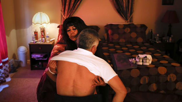 Lupita Ramirez dresses her husband, Joel, at their home in Rialto, Calif. Joel was paralyzed from the waist down after being crushed by a pallet when he was working in a warehouse. (Patrick T. Fallon for ProPublica)