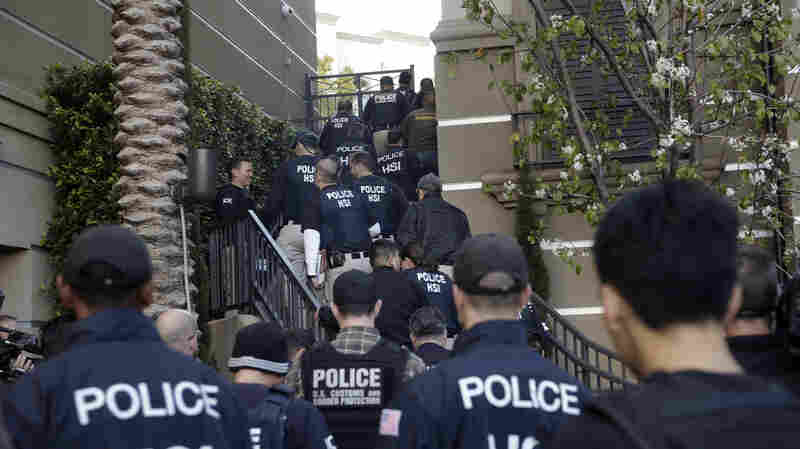Federal agents enter an upscale apartment complex, Tuesday in Irvine, Calif. Shortly after sunrise, federal agents swarmed the complex in the Orange County where authorities say a birth tourism business charged pregnant women $50,000 for lodging, food and transportation. The key draw for travelers is that the United States offers birthright citizenship.