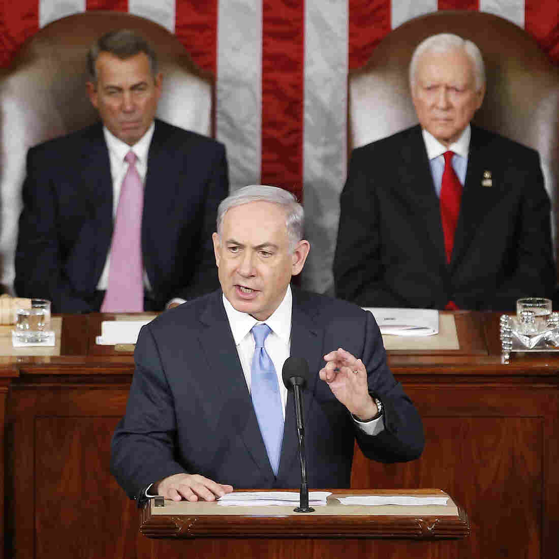 """Israeli Prime Minister Benjamin Netanyahu speaks before a joint meeting of Congress on Capitol Hill in Washington on Tuesday. Netanyahu said the world must unite to """"stop Iran's march of conquest, subjugation and terror."""" House Speaker John Boehner of Ohio (left) and Sen. Orrin Hatch, R-Utah, listen."""