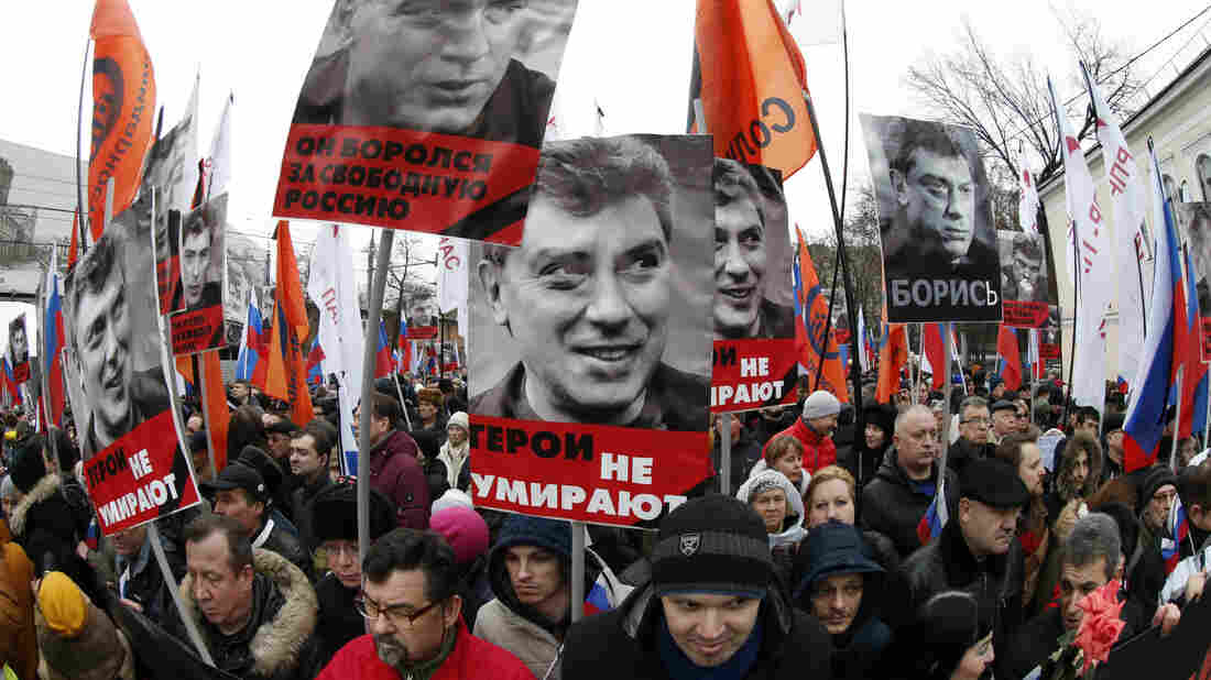 Russians hold flags and posters during a march to commemorate  Nemtsov.