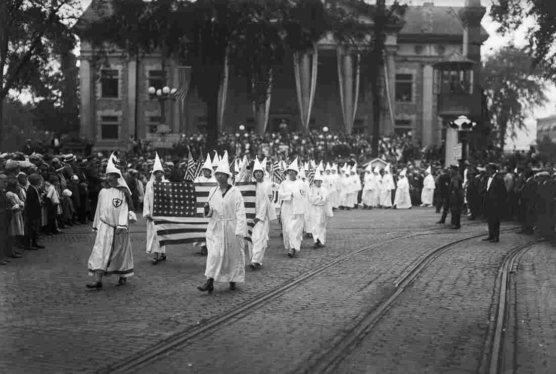 Female Ku Klux Klan members in the 1920s march through Binghamton, N.Y., holding American flags.