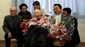 Misao Okawa, the world's oldest living person, poses for a photo with her son Hiroshi Okawa, 92, (left) and other family members and friends on her 117th birthday celebration at Kurenai
