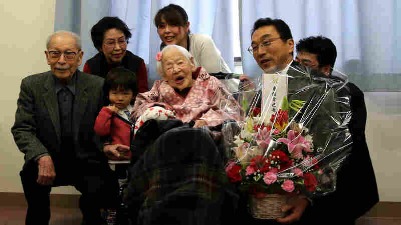 Misao Okawa, the world's oldest living person, poses for a photo with her son Hiroshi Okawa, 92, left, and other family members and friends on her 117th birthday celebration at Kurenai Nursing Home in Osaka, Japan.