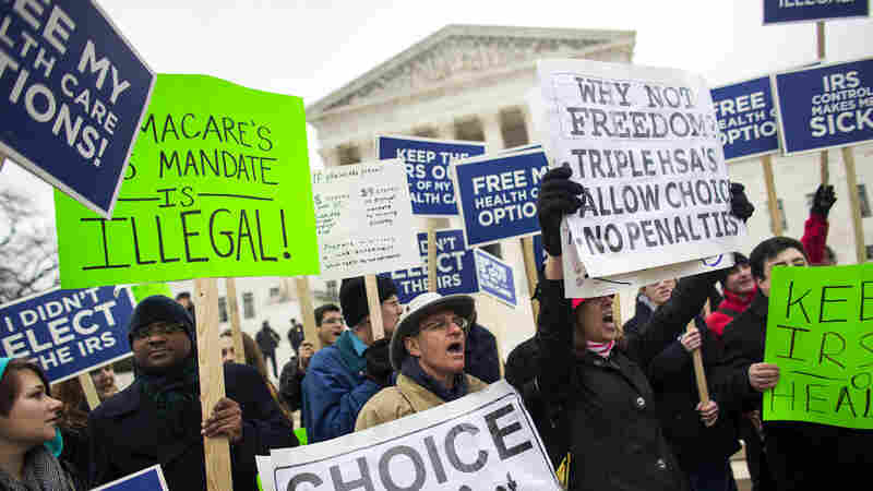 Opponents of the Affordable Care Act protest outside the Supreme Court Wednesday before oral arguments in the second major challenge to be heard by the justices.