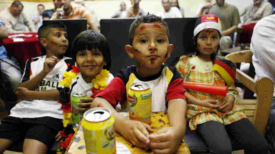 Young fans of the German national football team drink ice tea in July 2010 as they watch the FIFA World Cup semi-final match Germany vs Spain in an Arabic cafe in Berlin's Neukolln district. The neighborhood has gentrified rapidly in recent years, but many of the white families moving in leave once their children reach school age. Local groups are trying to change that.