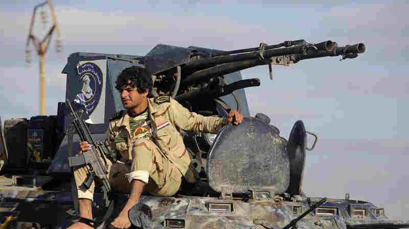 A Shiite fighter sits on a military vehicle in the town of Hamrin in Salahuddin province on Thursday.