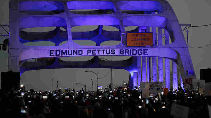 In this Sunday, Jan. 18, 2015, file photo, marchers hold up a their cellular phones to record the rapper Common and singer-songwriter John Legend performing at the foot of the Edmund Pettus Bridge.