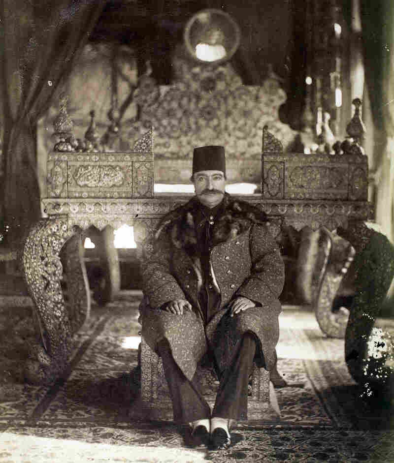 Nasir al-Din Shah, Iran's ruler at the time, sits on the lower step of the Peacock Throne in the Gulistan Palace, Tehran, during the late 19th century.