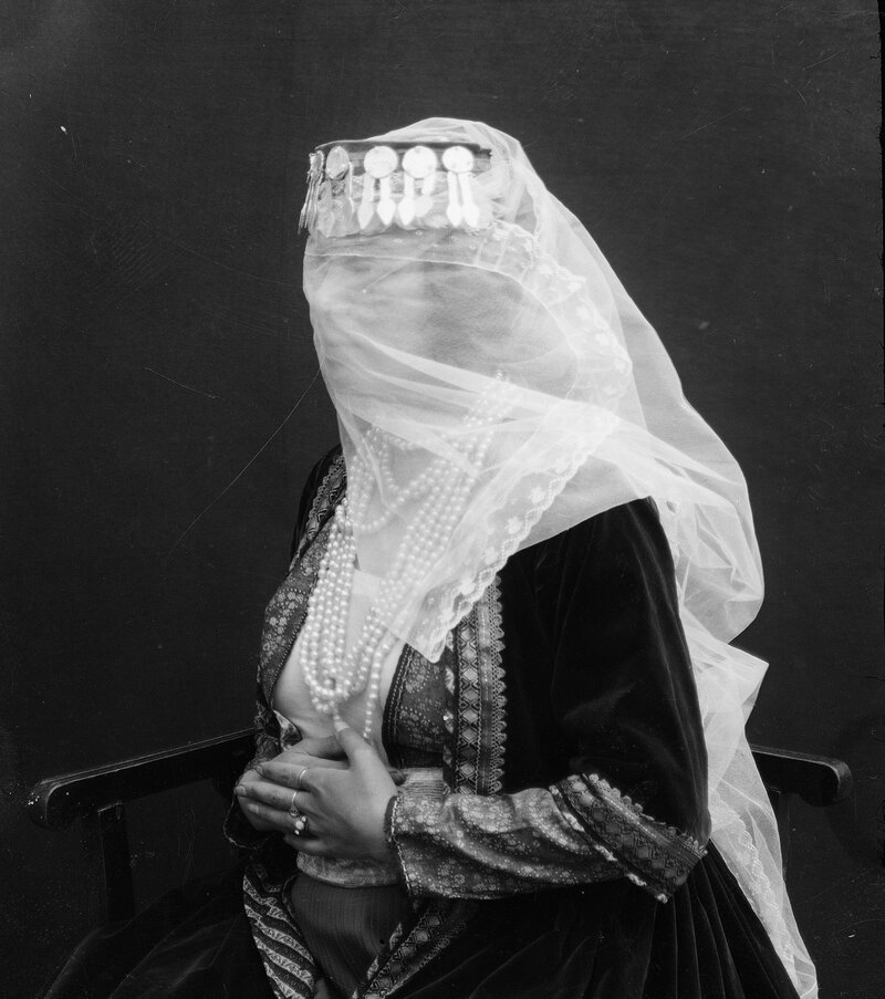 A woman wears a veil and pearls.