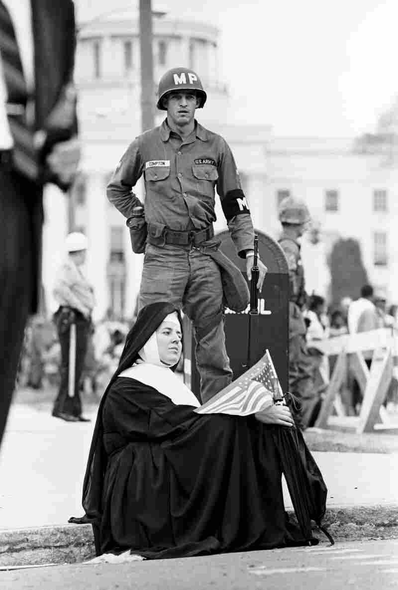 A nun and a national guardsman listen to Martin Luther King Jr. as the march ends in Montgomery.
