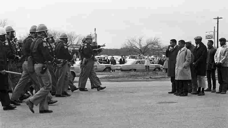 Spider Martin's most well-known photograph, Two Minute Warning, shows marchers facing a line of state troopers in Selma moments before police beat the protestors on March 7, 1965. The day became known as Bloody Sunday.