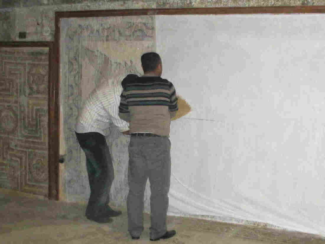 Syrian volunteers work to protect mosaics in the Ma'arra museum.