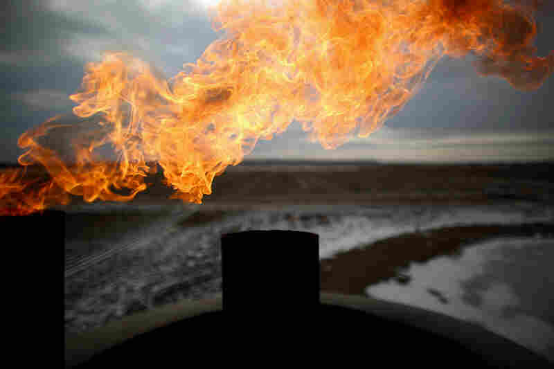 Natural gas is burned off at an oil well site near the city center of Sidney, Mont.