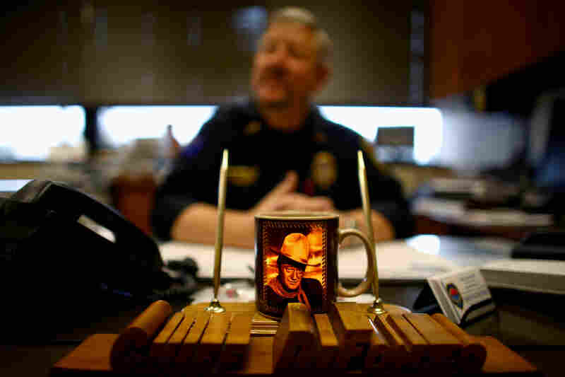 A coffee cup featuring John Wayne sits on the desk of Sidney's police chief, Frank DiFonzo. He has been chief since the last oil boom in the early 1980s. His caseload is enormous; crime is up tenfold and he's constantly playing catch-up.