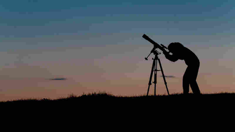 Female amateur astronomer observing the night sky.