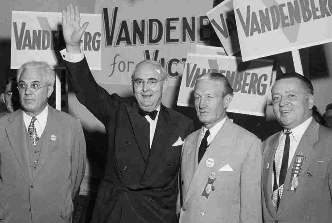"""Michigan Sen. Arthur Vandenberg, with arm raised, greets the press at the 1948 Republican Convention. Vandenberg worked closely with President Harry Truman's Democratic administration on foreign policy issues even though he was seeking the Republican nomination to challenge the president. """"Politics must stop at the water's edge,"""" Vandenberg famously said."""
