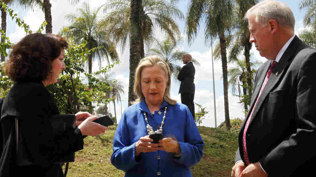 Then-U.S. Secretary of State Hillary Rodham Clinton (center) types on her cellphone with Roberta S. Jacobson, U.S. assistant secretary of state for Western Hemisphere Affairs (left), and U.S. Ambassador to Brazil Thomas Shannon in Brasilia, Brazil, before heading to Brussels in 2012.