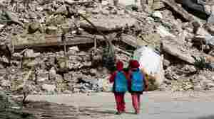 Girls carrying school bags provided by UNICEF walk past destroyed buildings on their way home from school on March 7 in the rebel-held al-Shaar neighborhood of Aleppo, Syria. So many people have fled the city and so much of its infrastr
