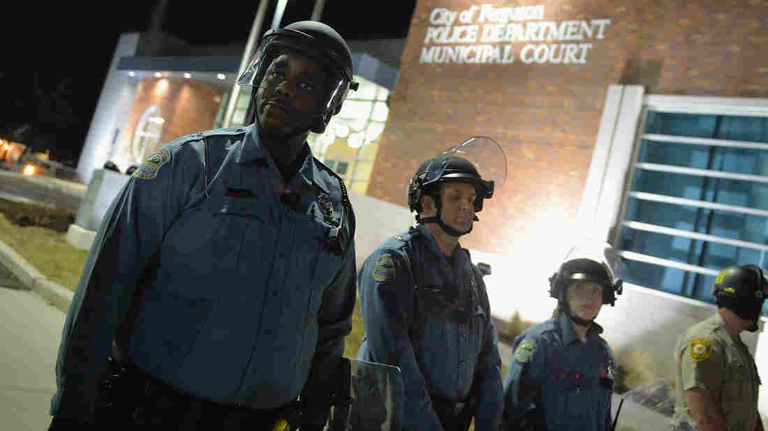 Police in riot gear respond to demonstrators blocking traffic during a protest Wednesday outside the Ferguson Police Department in Missouri. As the protests were ending, someone fired at the police and wounded two officers.