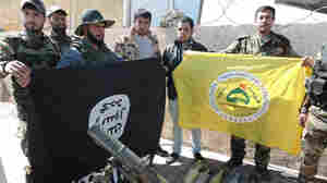 Shiite militiamen pose with their banner (right) next to a captured — and upside-down — ISIS flag (left) in Tikrit, Iraq. Militias are bolstering Iraqi forces in a major operation to retake the city from the self-proclaimed Islamic State.
