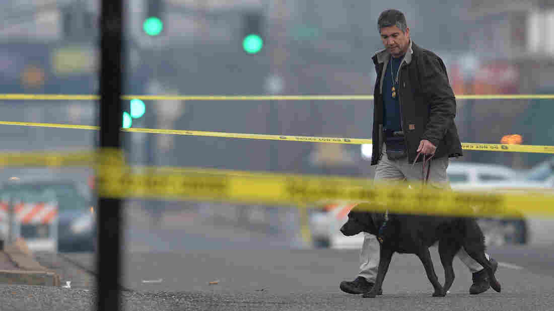 An agent with the Department of Alcohol Tobacco and Firearms arrives on the crime scene outside the Ferguson Police Department on Thursday. Just down the road, community leaders and residents have been struggling to digest this latest shock.