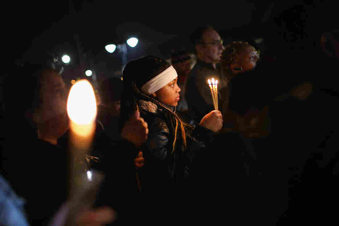 Demonstrators hold a prayer service near the Ferguson police station on Thursday. Prayers were said for both activists and the two police officers who had been shot earlier in the day.