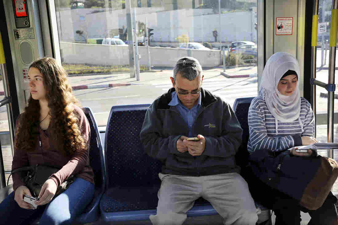 David Felber (center) rides the light rail, sitting between  Israeli and Palestinian university students. He lives in East Jerusalem and opposed the rail's route through Palestinian neighborhoods, but is now a regular rider.