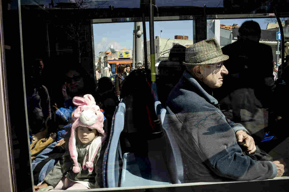 Riding on the rail line, Israeli children and adults alike are dressed for the Jewish holiday of Purim.