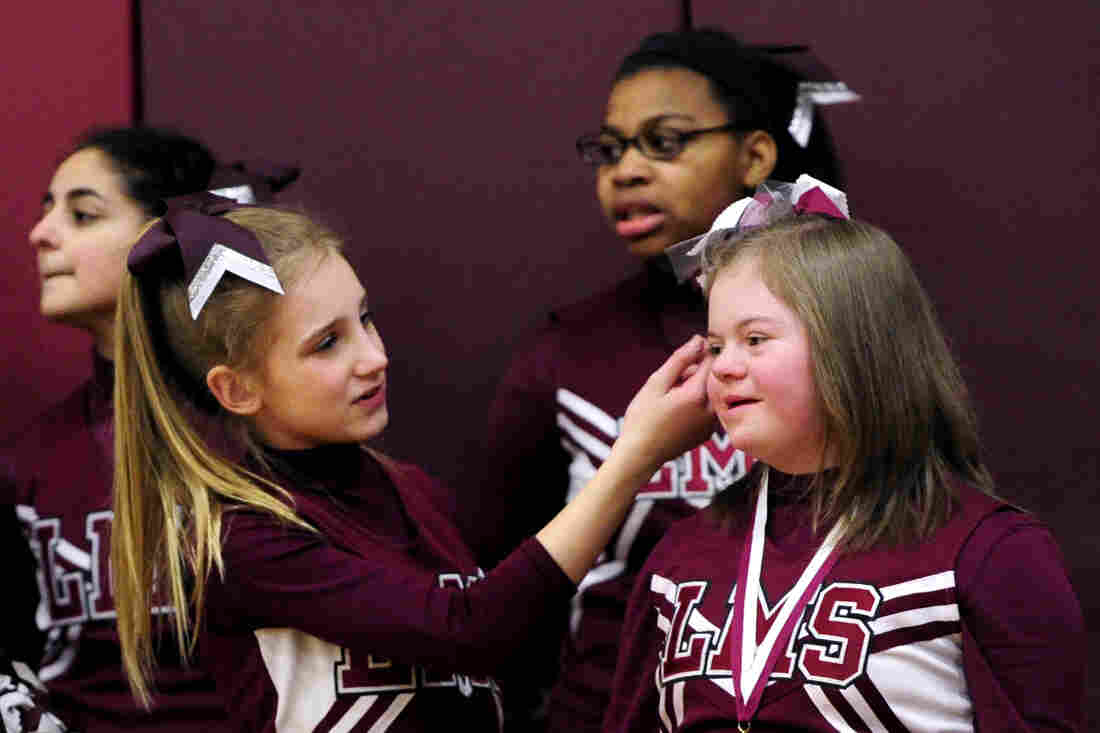 """Alyssa Smith readjusts Desiree Andrews' hair as they cheer for the seventh grade basketball team at Lincoln Middle School on Monday in Kenosha, Wis. The gym has been dubbed """"D's House"""" in Desiree's honor."""
