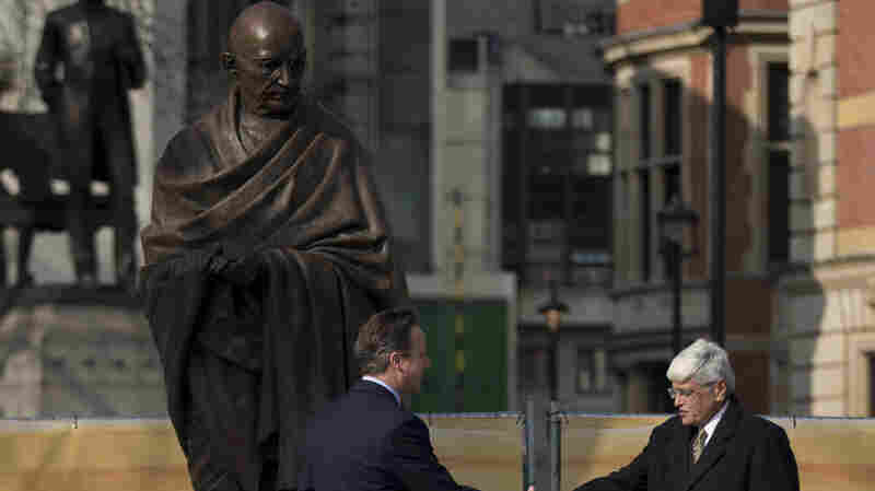 British Prime Minister David Cameron shakes hands with Gopalkrishna Gandhi, Mohandas Gandhi's grandson, beneath a new statue of the Indian independence leader by British sculptor Philip Jackson, after it was unveiled today in London's Parliament Square.