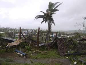 In this March 14, 2015, photo provided by World Vision, debris is strewn around a lone tree in Port Vila, Vanuatu, after Cyclone Pam ripped through the tiny South Pacific archipelago.