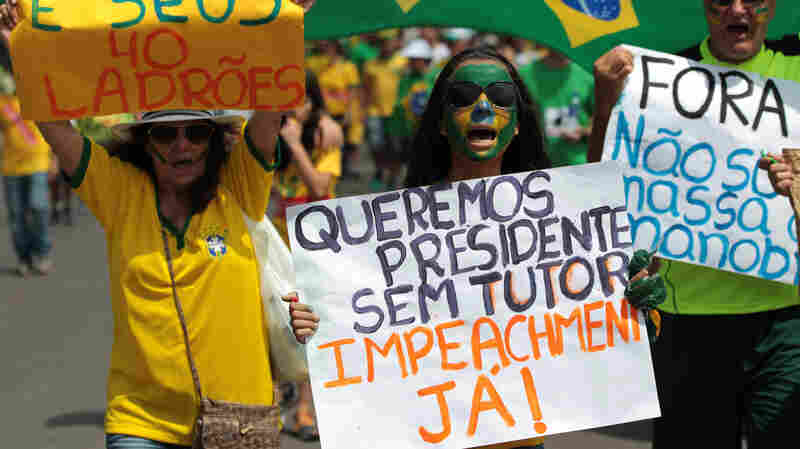 "A family carries posters with ""Dilma out and Impeachment Now,"" written in Portuguese, during a protest Sunday in the capital, Brasilia."