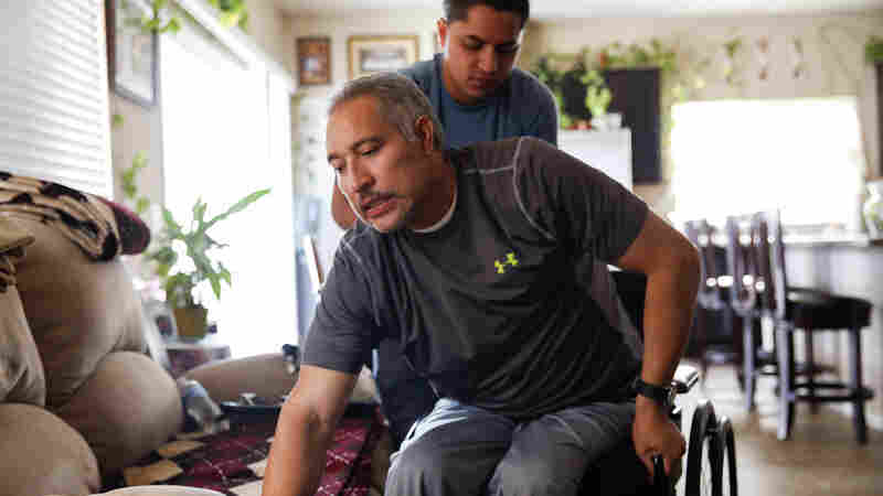 Joel Ramirez climbs back into his wheelchair with the help of Francisco Guardado, a home health aide, at his home in Rialto, Calif.