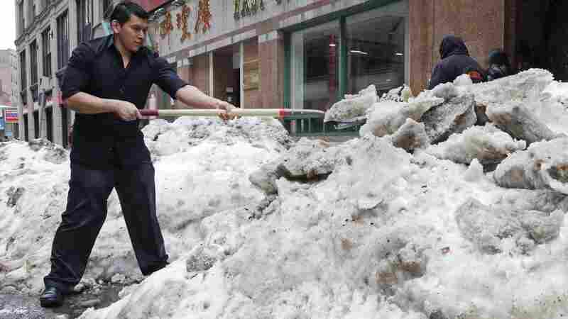 A waiter shovels snow outside the restaurant he works at in the Chinatown neighborhood of Boston.