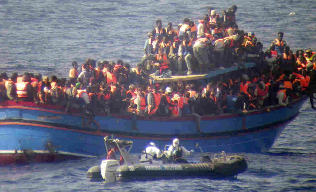 A motorboat from the Italian frigate Grecale approaches a boat overcrowded with migrants in the Mediterranean Sea on June 29, 2014. The boat was carrying nearly 600 people, and the remaining 566 survivors were rescued.