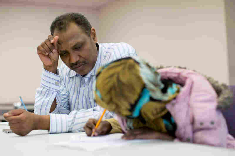 "Shekhey helps a child with homework at the after-school program. Shekhey says he and his staff aim to help refugees feel at home. ""We are like soldiers,"" he says. ""We go do whatever's needed. No time sheets, no nothing. Just go."""